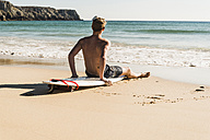 Teenage boy sitting on surfboard at the sea - UUF08442