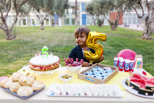 Little boy with golden balloon behind laid birthday table - VABF00770