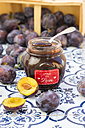 Preserving jar of homemade plum jam and plums on tiles - LVF05297