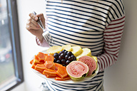 Woman holding plate with fresh fruit - KNTF00488
