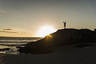France, crozon peninsula, young man on rock at sunset - UUF08485
