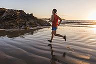 France, Crozon peninsula, jogger on the beach at sunset - UUF08488