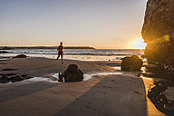 France, Crozon peninsula, jogger on the beach at sunset - UUF08494