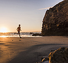France, Crozon peninsula, jogger on the beach at sunset - UUF08497