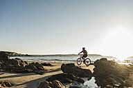 France, Crozon peninsula, Man biking on the beach - UUF08503
