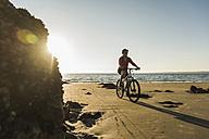 France, Crozon peninsula, Man biking on the beach - UUF08506