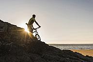 France, Crozon peninsula, mountainbiker looking at sunset - UUF08512