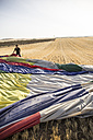 Man packing up a hot air balloon envelope in field - ABZF01240