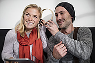 Young man sharing headphones with young woman - ZEF10373