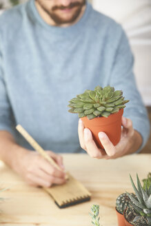 Man holding succulent plant and taking notes - RTBF00357
