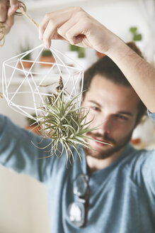 Young man putting air plant in a pendant - RTBF00360