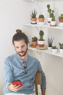 Young man with a collection of cacti looking on cell phone - RTBF00363