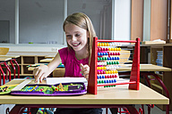 Smiling schoolgirl sitting at desk in her class - SARF02876