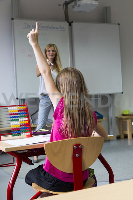 Back view of schoolgirl raising her hand - SARF02879