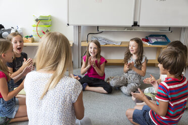 Teacher and pupils sitting on floor of their classroom singing and clapping hands - SARF02894