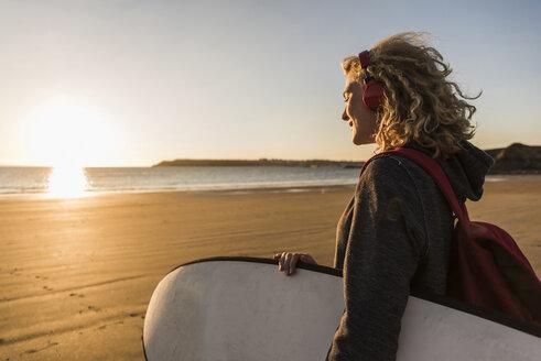 Teenage girl on the beach carrying surfboard - UUF08540