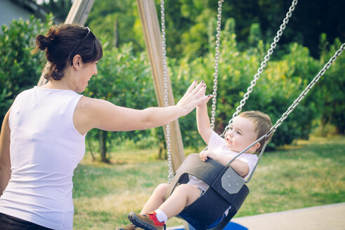Baby boy sitting on a swing watching his mother - JPSF00006