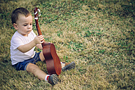 Baby boy sitting on a meadow with ukulele - JPSF00009