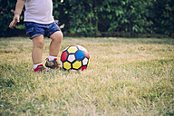 Baby boy playing soccer on a meadow, partial view - JPSF00012