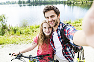 Young couple taking selfies on a bicycle trip - HAPF00854