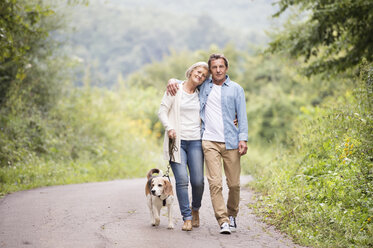 Senior couple on a walk with dog in nature - HAPF00869