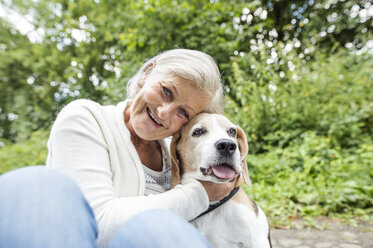 Happy senior woman cuddling her dog - HAPF00887