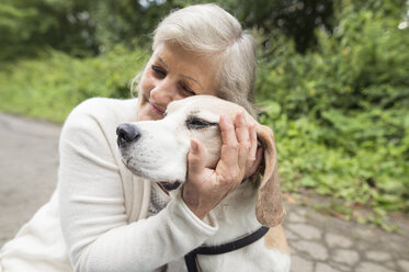 Happy senior woman cuddling her dog - HAPF00890