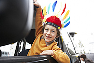 Boy with feather headdress looking out of car window - FSF00457