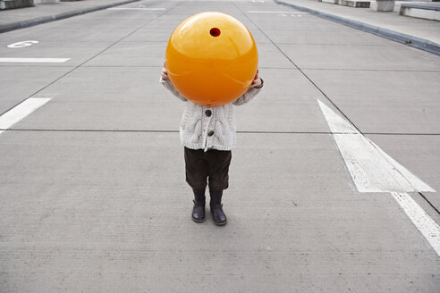 Little girl standing in street, hiding under orange sphere - FSF00487