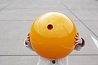 Little girl standing in street, hiding under orange sphere - FSF00490