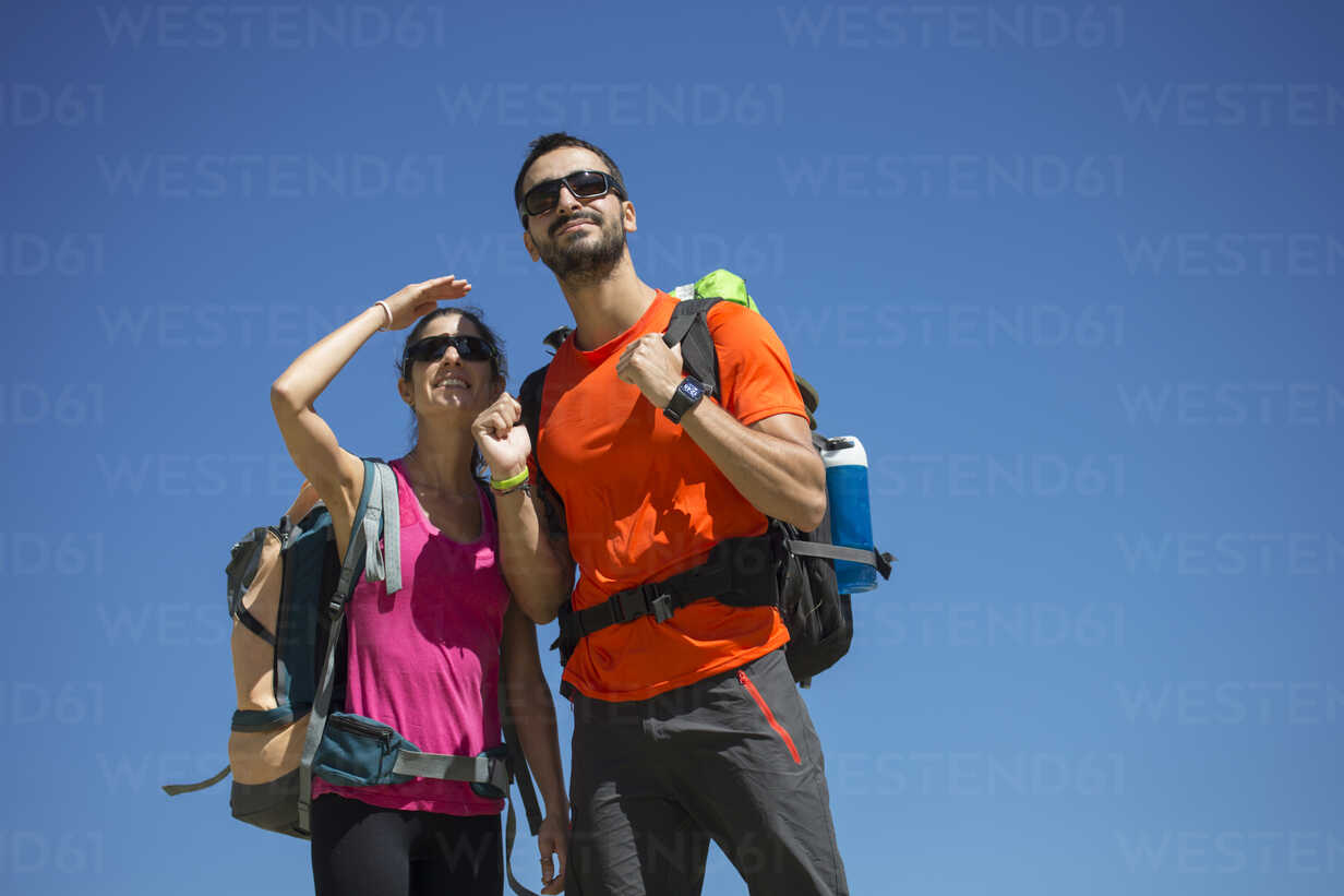 Hiking couple looking out under blue sky - ERLF00187 - Enrique Ramos/Westend61