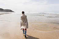 Mature woman walking on the beach - UUF08562