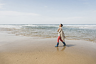 Mature woman walking on the beach - UUF08565