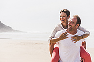 Happy mature man carrying wife piggyback on the beach - UUF08574