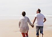 Mature couple running on the beach - UUF08577