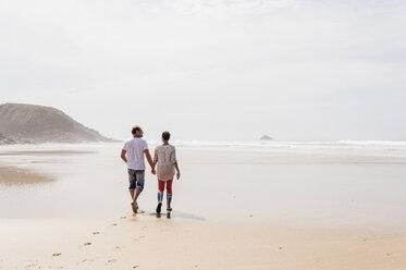 Mature couple walking on the beach - UUF08580