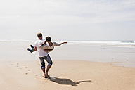 Mature man carrying his wife on the beach - UUF08583