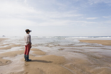 Mature woman standing on the beach wearing VR glasses - UUF08586
