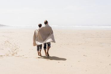 Mature couple walking on the beach - UUF08595