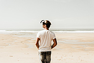 Mature man standing on the beach wearing VR glasses - UUF08598