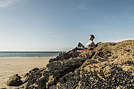 Mature woman relaxing on rock at the beach - UUF08601