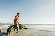 Mature woman walking with dog at the sea - UUF08607