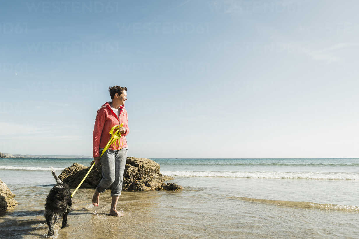 Mature woman walking with dog at the sea - UUF08607 - Uwe Umstätter/Westend61