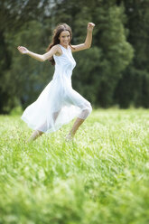 Happy woman wearing white summer dress on a meadow - MAEF12020