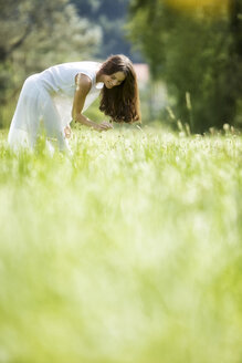 Happy woman wearing white summer dress picking flowers on a meadow - MAEF12023