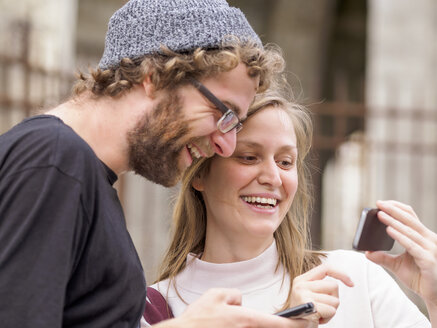 Smiling young couple looking at smartphone - LAF01729