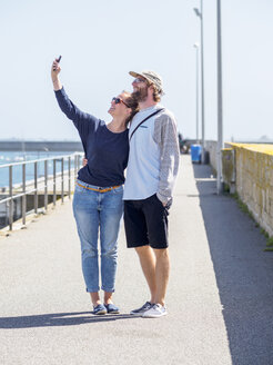 France, Bretagne, Finistere, happy young couple taking selfie with smartphone at harbour - LAF01732