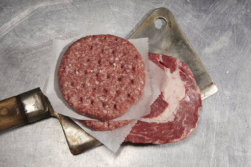 Raw beef steak and burger patty on cleaver - SCF00444