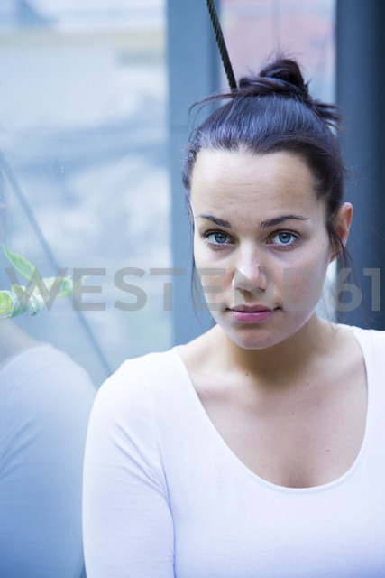 Portrait of serious young woman leaning against windowpane - NGF00372 - Nadine Ginzel/Westend61