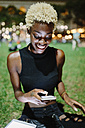 Smiling young woman sitting on meadow of a park at night text messaging - GIOF01463